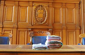 Photos d'un tribunal avec des dossiers en premier plan et le symbole de la justice gravée dans le bois en fond